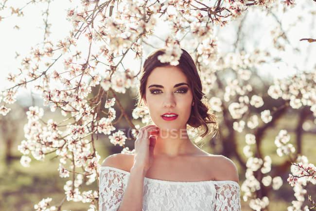 Молодая женщина между миндаль цветы в саду весной — стоковое фото