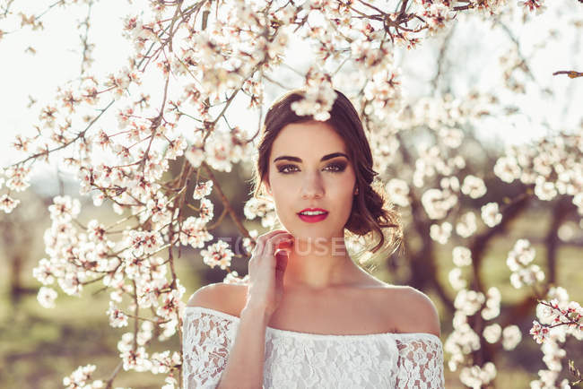 Young woman between almonds flowers in spring garden — Stock Photo