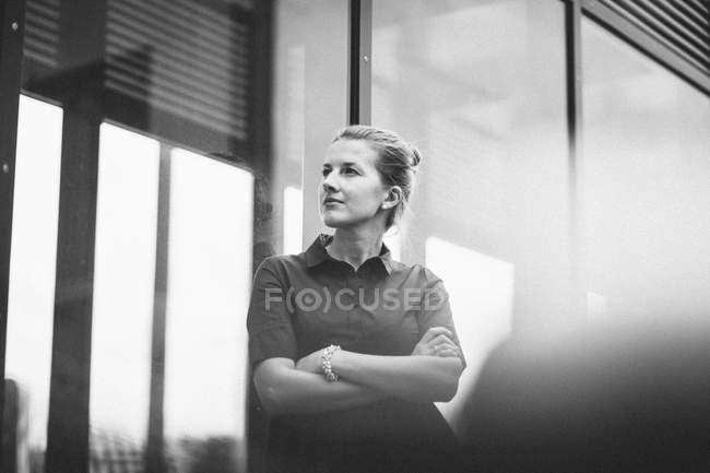 Caucasian woman standing with arms crossed and looking away — Stock Photo
