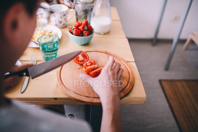 Man cutting tomatoes at breakfast table in the morning — Stock Photo