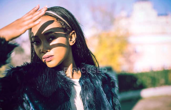 Donna africana in cappotto di pelliccia che guarda l'obbiettivo e che copre il viso dal sole — Foto stock