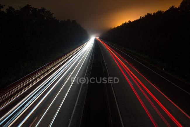 Tir longue exposition des sentiers de lumière sur l'autoroute de nuit — Photo de stock