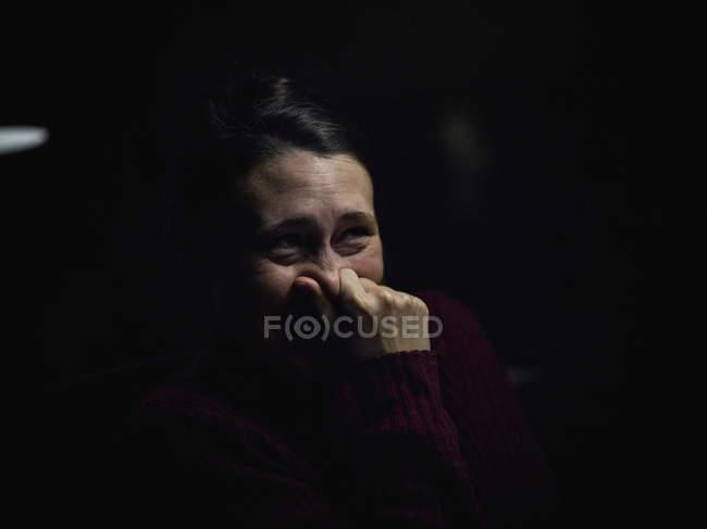 Donna contro una priorità bassa nera, toccando il suo naso — Foto stock