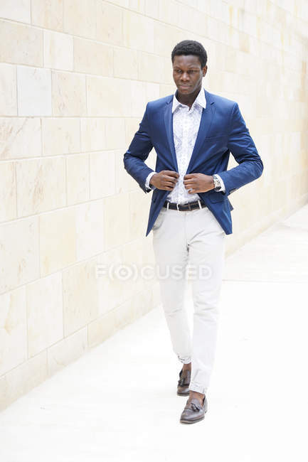 Full length shot of young man walking in street and adjusting blue jacket — Stock Photo