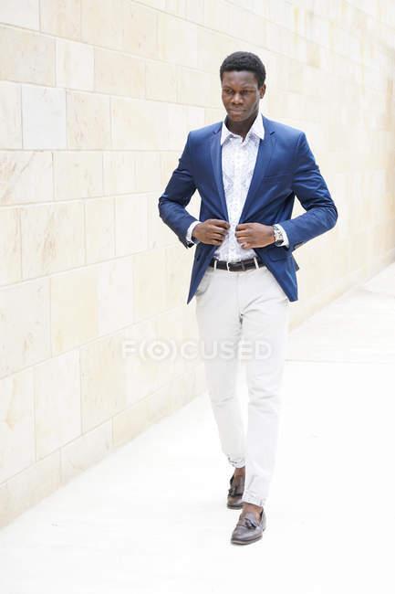 Повна довжина постріл молодий чоловік ходьби вулиці і коригування блакитний жакет — стокове фото
