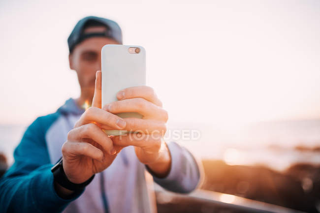 Stylish guy holding mobile phone while standing outdoors at sunset — Stock Photo