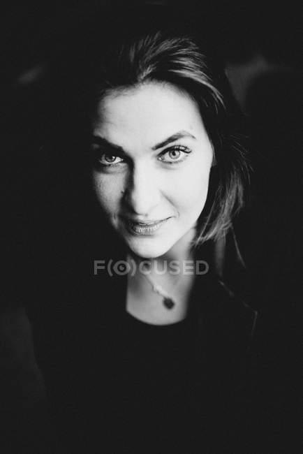 Portrait der schönen Frau, Blick in die Kamera auf schwarzem Hintergrund — Stockfoto