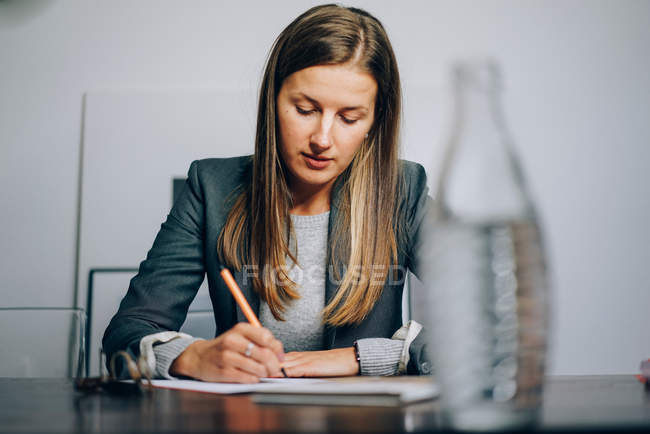 Teacher woman writing on paper with pen — Stock Photo