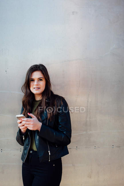 Young woman using phone while standing against neutral wall — Stock Photo