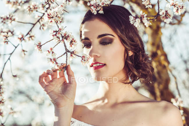 Young woman smelling almond flowers in from tree branches — Stock Photo