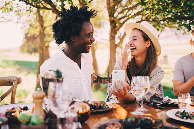 Cute mixed race couple enjoying lunch outdoors and browsing mobile phone — Stock Photo