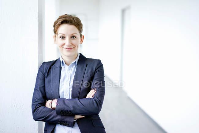 Retrato de mulher jovem sorridente em pé com os braços cruzados — Fotografia de Stock