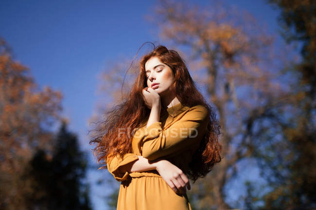 Young redheaded model woman in yellow dress — Stock Photo
