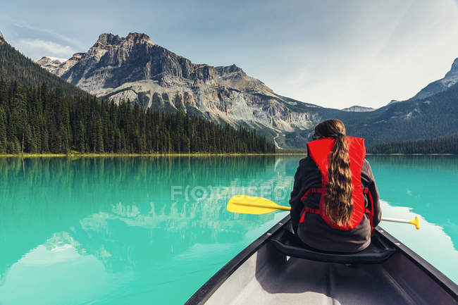 Woman sitting in canoe boat and overlooking clear water and mountains in Banff National Park — Stock Photo
