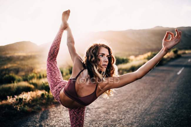 Young woman doing yoga pose outdoor — Stock Photo