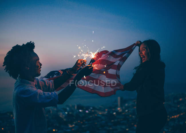 African man and girl celebrating with usa flag and sparkler — Stock Photo