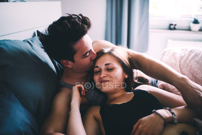 Cheerful couple enjoying time together in bed and kissing — Stock Photo