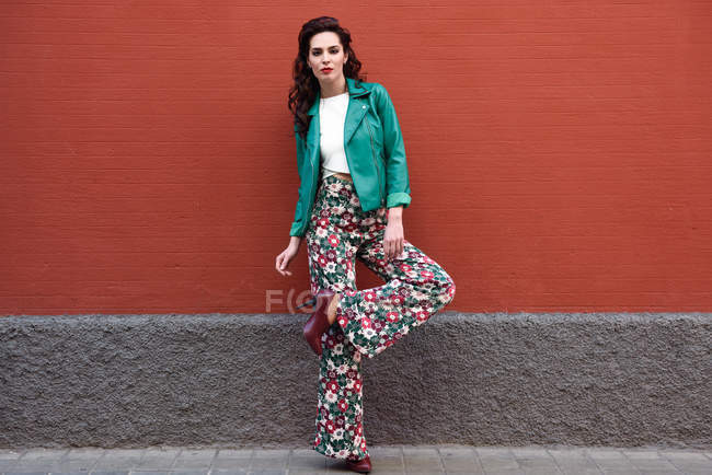 Full length of stylish Caucasian woman posing at red wall — Stock Photo