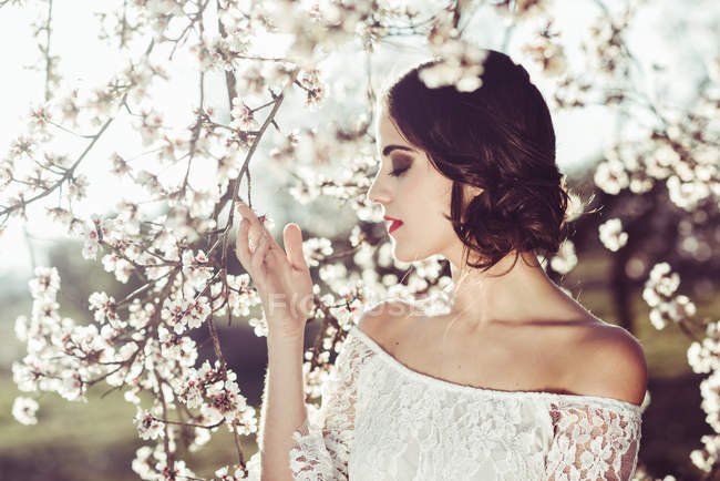 Young woman smelling almond flowers in springtime — Stock Photo