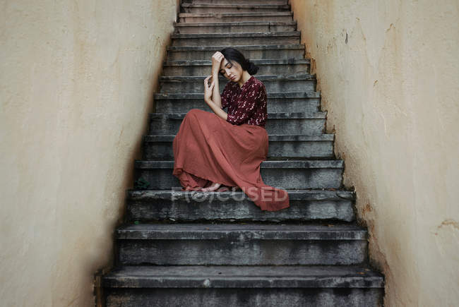 Woman in long red skirt sitting on steps — Stock Photo