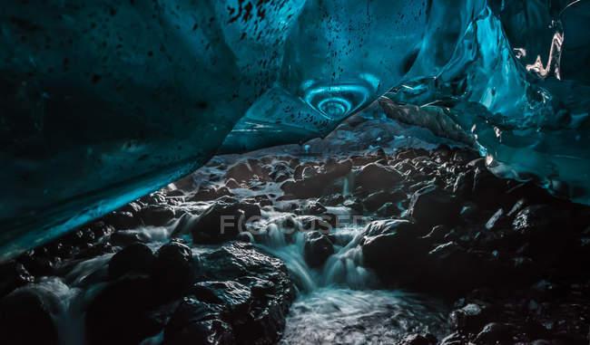 Water flowing inside frozen glacier cave — Stock Photo