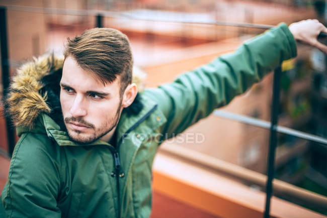 Handsome young man in green parka jacket looking away — Stock Photo