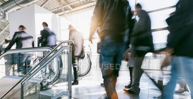 Bewegungsunschärfe von Gruppen von Menschen zu Fuß auf Flughafen — Stockfoto