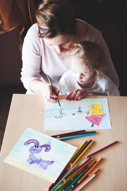 Mother and daughter coloring art pictures a table — Stock Photo