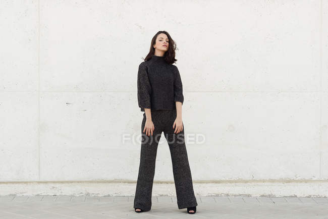Fashion woman in black clothes posing outdoors at wall — Stock Photo