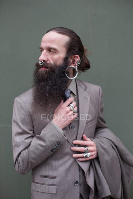 Fashion portrait of bearded hipster man wearing lots of jewelry — Stock Photo