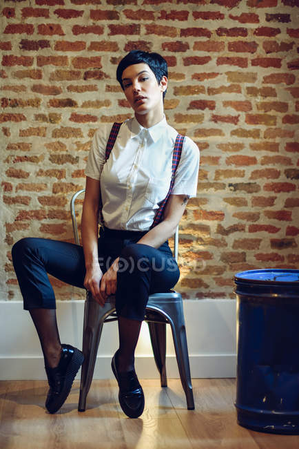 Full length of woman with short hair wearing shirt with suspenders and posing at brick wall — Stock Photo