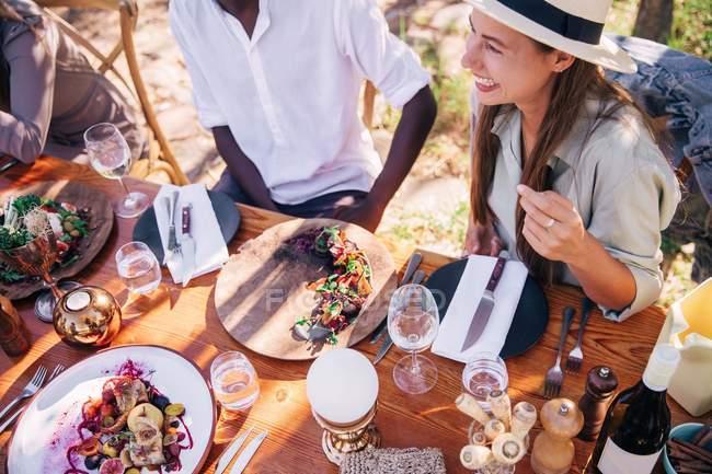 Groupe de personnes ayant des repas à la table en bois à l'extérieur — Photo de stock