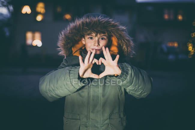 Petite veste d'hiver usure garçon avec capuche et gesticulant coeur avec les doigts — Photo de stock
