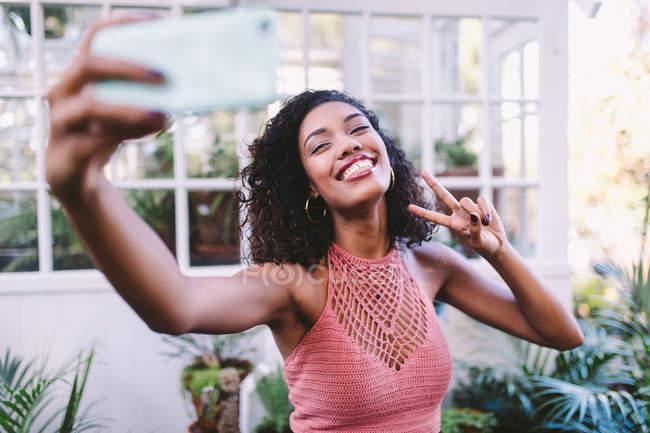 Lächelnde junge Frau nehmen Selfie auf Handy und gestikulierte Peace-Zeichen — Stockfoto