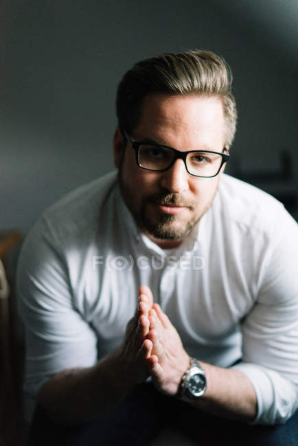 Young bearded man wearing eyeglasses and looking at camera — Stock Photo