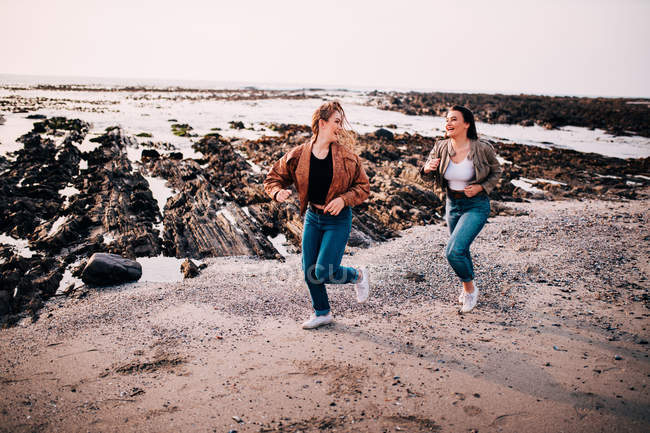 Best friends, Women running on beach and laughing — Stock Photo