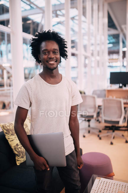 Portrait of smiling confident afro american man looking at camera and holding laptop — Stock Photo