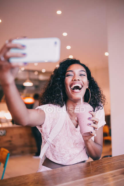Happy African woman taking selfie and holding smoothie drink — Stock Photo
