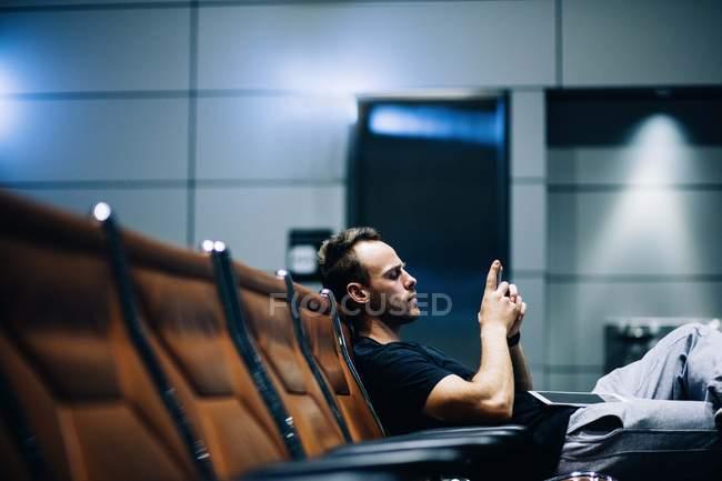 Молодий чоловік, за допомогою смартфона, сидячи на лавці, чекаючи на рейс — стокове фото