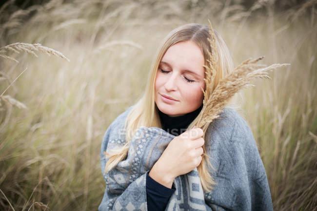 Donna che tiene pianta erba di campo e coperto di coperta — Foto stock