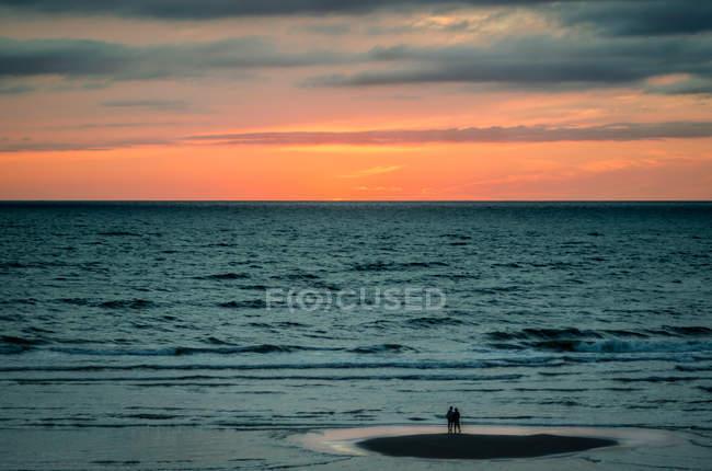 Deux personnes embrassant sur une plage à l'eau de mer avec coucher de soleil dans le ciel — Photo de stock