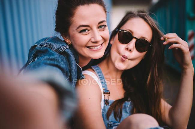 Zwei glückliche Freundinnen unter Selfie und lustige Gesichter — Stockfoto