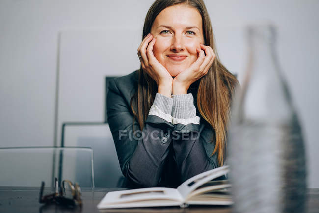 Smiling woman sitting at desk with book and looking at camera while keeping hands on chin — Stock Photo