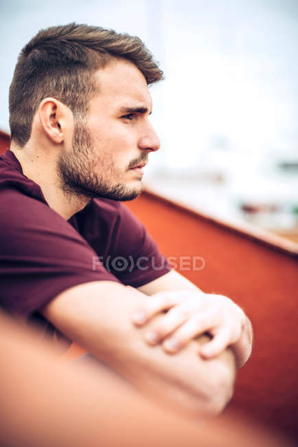 Handsome young Caucasian man with stubble sitting with arms crossed and thinking — Stock Photo