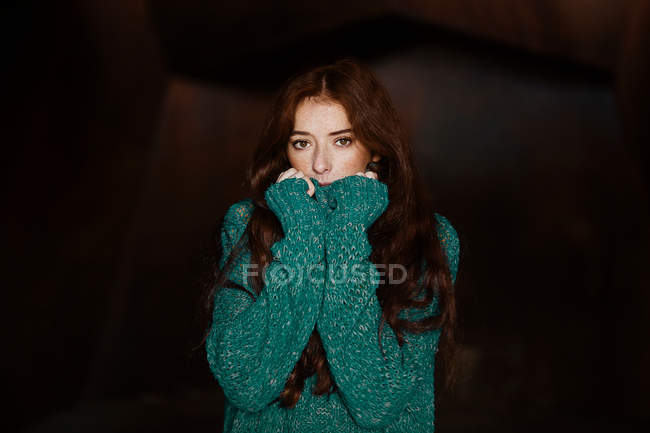 Redheaded caucasian woman with long hair and in green sweater looking at camera — Stock Photo