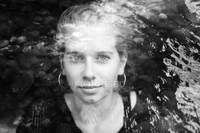 Portrait of sensual woman looking at camera, water ripple surface, black and white photo — Stock Photo