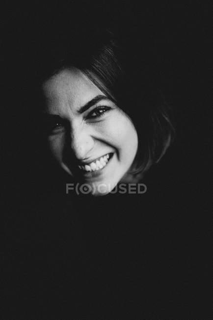 Porträt der lächelnde Frau, Blick in die Kamera auf schwarzem Hintergrund — Stockfoto