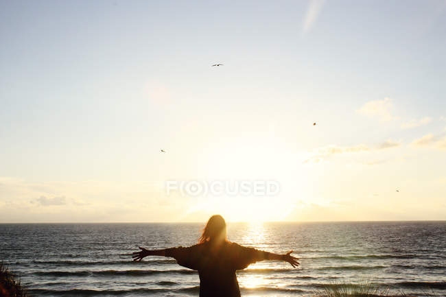 Rear view of woman standing at beach during sunset — Stock Photo
