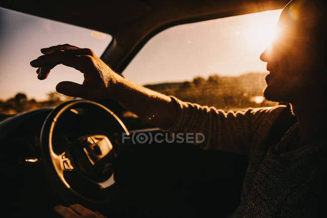 Young happy adult men driving car in sunset — Stock Photo