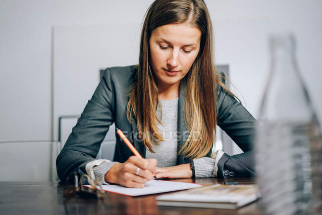 Business woman sitting at her desk and writing notes on paper with pen — Stock Photo